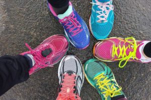 Six different coloured trainers all pointing inwards in a circle