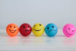 Five different coloured ping pong balls with different emoji style faces drawn onto them