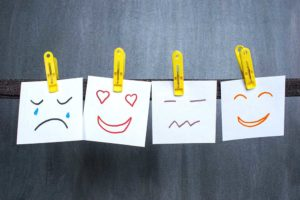 Four different emoji style faces drawn on four post-it-notes pegged onto a line