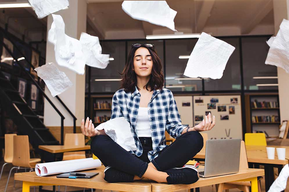 A young woman is sitting on a desk in a meditation pose with her eyes closed as papers fly about around her