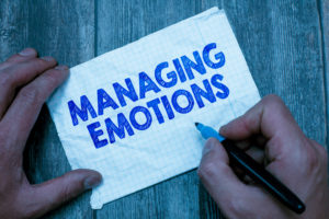 The word MANAGING EMOTIONS written on a piece of paper with a marker pen