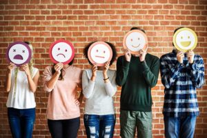 A group of young people hold cutouts of emoji faces in front of their own faces