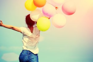 A young woman is running whilst holding a bunch of balloons