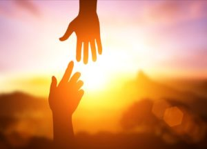 Two hands reaching for each other with a sunset in the background
