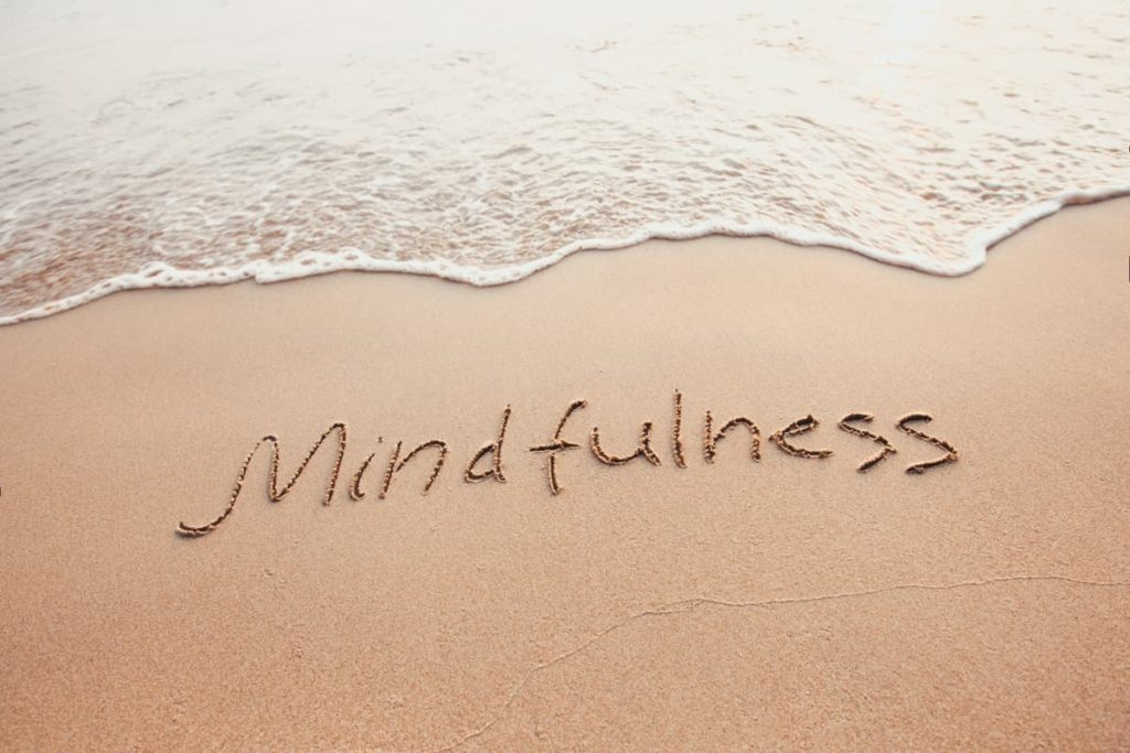 Waves lapping on the shore with the word Mindfulness written in the sand on the beach