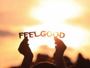 A paper cutout of the words FEEL GOOD held up against a sunset background