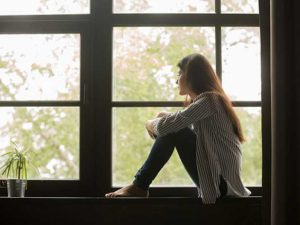 A young woman sits hugging her knees, looking out of a large window