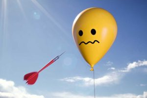 A photo of a dart flying towards a balloon with a worried face on it