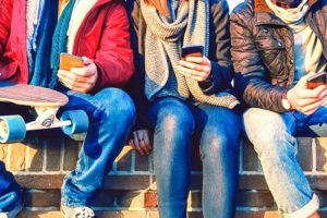 A photograph of Three people sitting on a wall checking their smartphones