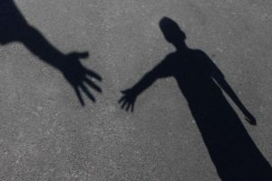 A shadow on the ground of an adult's hand reaching for a young person's outstretched hand