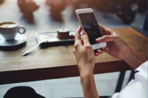 A photo of a person sitting in a coffee shop checking their smartphone