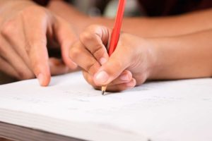 A young adult's hand writing on paper with a pencil, being guided by another hand