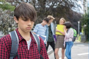 A photo of a young man looking sad in the foreground, with a group of young people who seem to be talking about him behind his back in the background