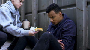 A teenage boy kneeling down to offer a takeaway cup and a sandwich to another boy sitting on the floor