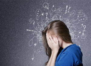 A photo of a teenage girl facing sideways with her hands covering her face, and on the background all around her head are chalk drawn squiggly lines in all directions, some with words such as 'ideas', lightbulbs, exclamation marks, question marks, arrows, ellipses.