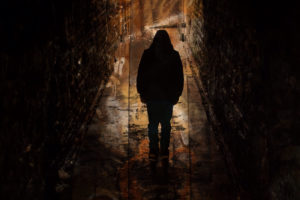 A dark hooded figure walking alone away from the camera down a dark alleyway with high brick walls on both sides of the photo.