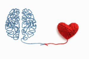 On a white background, to the left is a piece of blue wool laid down in the pattern and shape of a human brain, leading into the middle tied in a knot with a red piece of wool that leads off to the right to a heart shape made out of red wool.