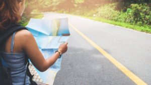 A photo of a teenage girl in the bottom lefthand corner facing away from the camera wearing a backpack, holding out a map in both hands, facing towards a road that goes off into the distance.