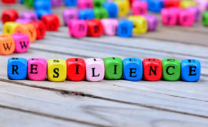 A photo of individually coloured dice placed in a row that have the letters on that spell the word 'resilience' and other random lettered dice in the background