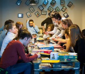 A photo of a room with a long rectangular table down the middle of the image covered in board games and the table is surrounded by teenage friends all playing different games together.