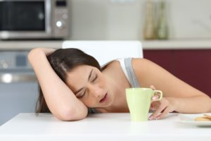 Girl fallen asleep on table top with mug in hand