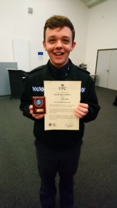 A photograph of VPC Mothersole smiling and holding a certificate