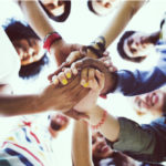group of friends with hands together in the middle