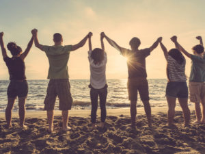 Multiracial group of people with raised arms looking at sunset. Backlight shot. Happiness, success, friendship and community concepts