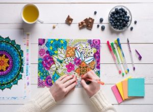 A photo of someone colouring in a mindfulness colouring sheet, with post it notes, pens, healthy food and a drink around the outside of the image.